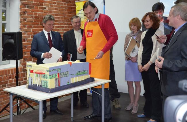 Кульминация вечера - архитектор Алексей Каменюк приступает к разрезанию торта в виде его проекта школы Олимпийского резерва.