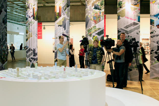 Стенд Москомархитектуры. Тележурналисты ждут прихода Марата Хуснуллина. Арх Москва 2017.  Фотография © Юлия Тарабарина, Архи.ру