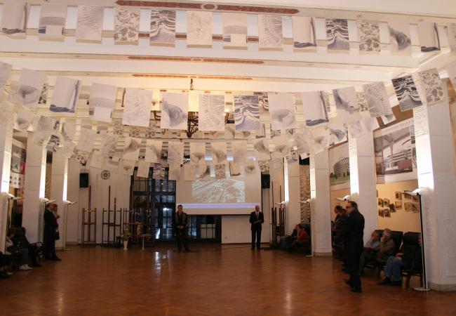 Развешанные под потолком чертежи напоминают праздничные гирлянды и придают выставке особое приподнятое настроение