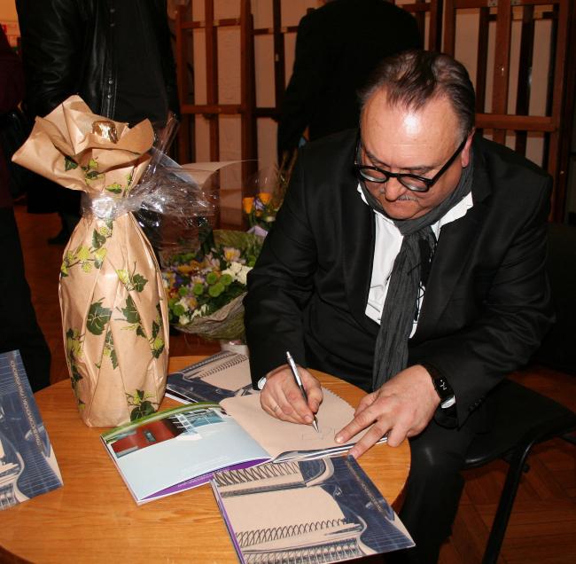 Ю.Г.Виссарионов раздает автографы на специально выпущенных к открытию выставки буклетах с работами мастерской