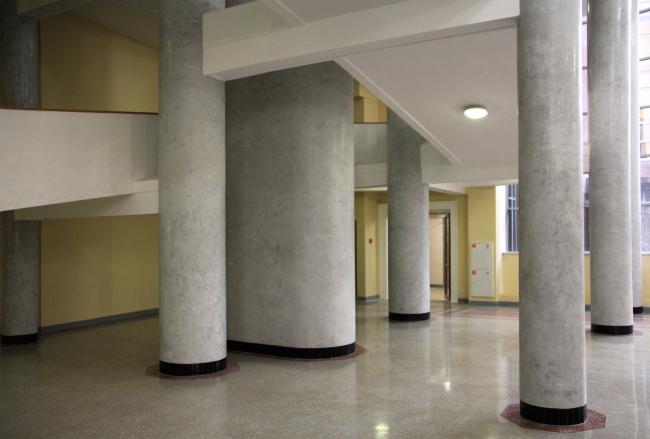 Столбы вестибюля: тонкие круглые и среди них – широкие столбы элиптического сечения, которые продолжаются вверху, в на сцене в аудитории. Столбы пронизывают здание насквозь, оно «надето» на опоры. Фотография Ю. Тарабариной
