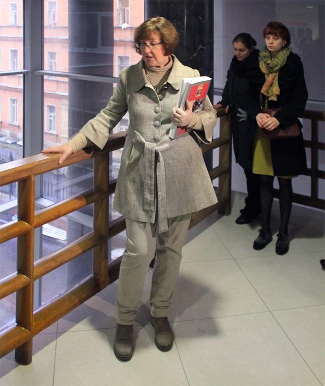Елена Гонсалес показывает деревянные перила 1930-х годов. Пол второго этажа вестибюля отступает от витража, и получается балкон. Фотография Ю. Тарабариной