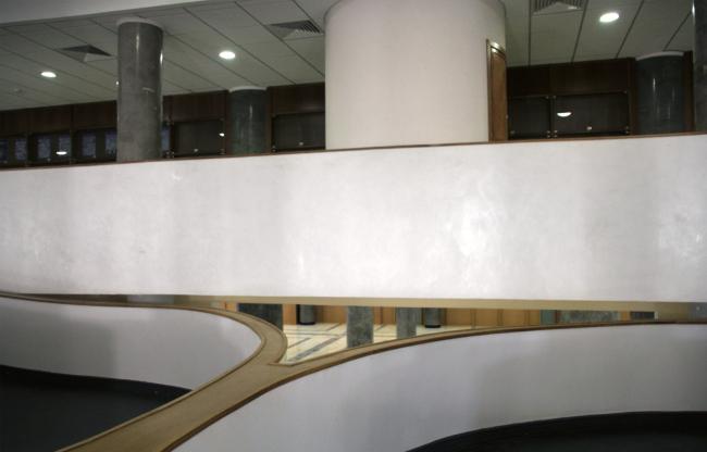 Пандусы вестибюля. В зазоре между пандусами и балконом виден интерьер зала второго этажа, что делает интерьер как-то особенно проницаемым. Фотография Ю. Тарабариной