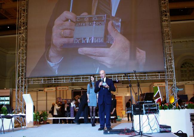 Андрей Боков держит в руках награду Александр Кузьмина за «Честь и достоинство»