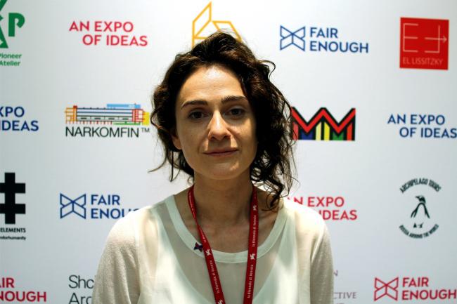 Сокуратор павильона Дарья Парамонова перед брендволом с логотипами воображаемых фирм. Фотография Юлии Тарабариной