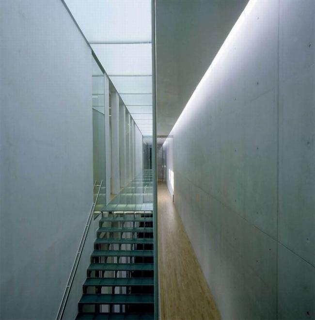 Штаб-квартира Bang & Olufsen в Струере. В этом узком коридоре с прозрачным антресольным этажом  полоса  солнечного света сверху  играет с фактурой бетонной стены.  Из отстраненно – стального он  будто переходит в мягкое бархатистое состояние. Предоставлено Velux