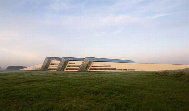 Завод Fiberline Middelfart. Удивительно, как архитектура завода настроена на восход и закат солнца!  Ян Сондергаард  учел ориентацию  комплекса восток-запад  и, в  зависимости от времени суток,  холм то  «вырастает», то едва прорисовывается,  а полосы остекления  похожи  на речки и  ручьи. Предоставлено Velux