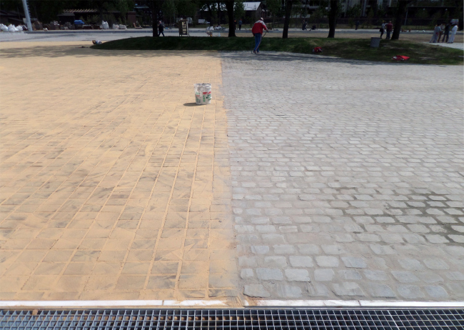 On the left: flooring of wooden cubes. On the right: stone pavement. Photograph © Ilia Mukosey