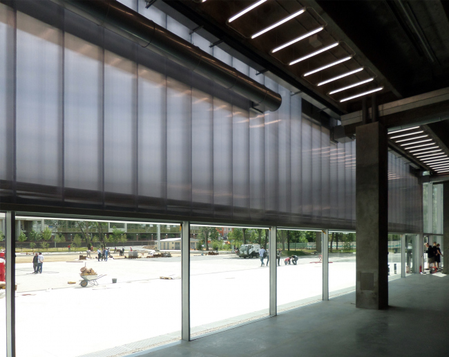 The polycarbonate facade starts two meters up from the ground. The concrete floor of the foyer is the same level with the outside ground. Photograph © Ilia Mukosey