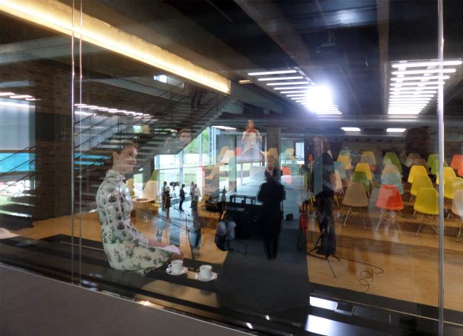 "Rem Koolhaas (behind the glass) gives an interview on the day of the inauguration of the new building of the ""Garage"". Photograph © Ilia Mukosey"
