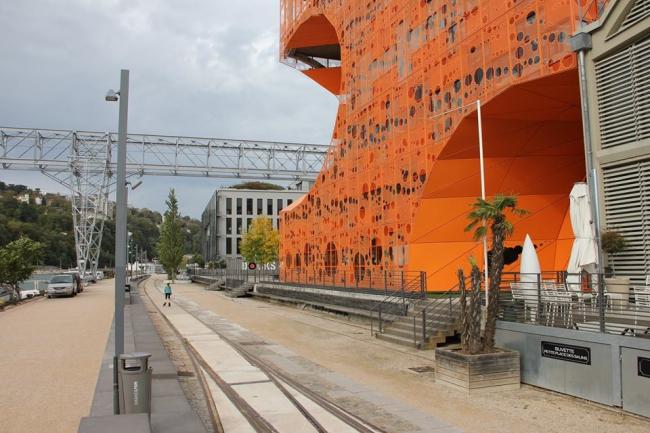«Лион, район Конфлуанс, набережная Рембо. На бывших портовых территориях с сохранившимися старыми складами появление здания RBC LYON 42 (Orange Cube) весьма убедительно показало, насколько появление Showroom concept в радикально новой интерпретации синтеза Архитектура + Дизайн + Реакция-на-среду может изменить образ и смысл места, сохранив в нем исторический «дух»... Никаких комплексов «трепетной» консервации наследия, но масса позитивных эмоций от реально инновационной архитектуры». Текст и фотография © Валерий Нефедов