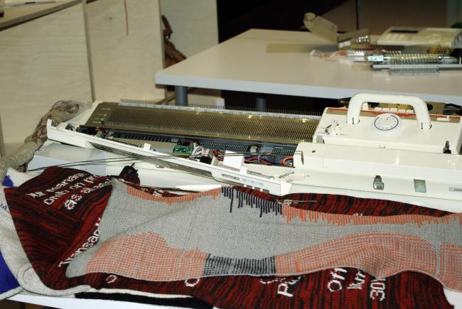 Образцы, связанные на «взломанной» роботизированной машине, и сама вязальная машина с роботом в галерее SuperSurfaceSpace. Фотография Аллы Павликовой