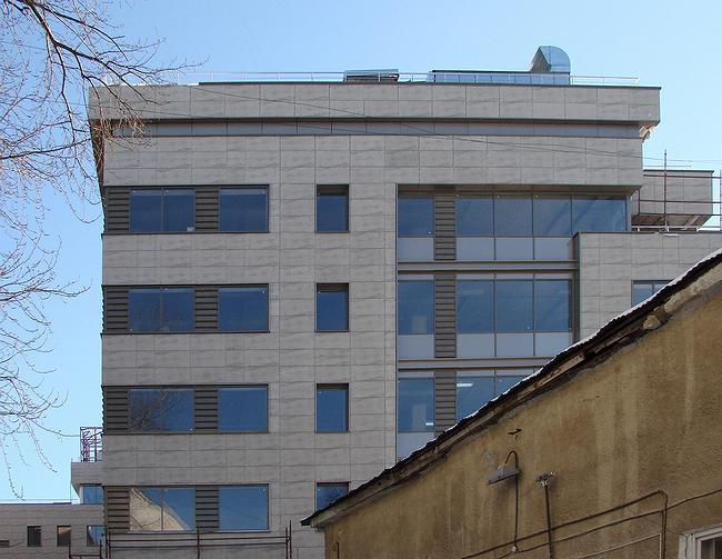Западный фасад, выходящий внутрь квартала – пример очень спокойной офисной архитектуры. Но и он не лишен интриги – горизонтальные ленты, похожие на ленточные окна, соседствуют с окнами обыкновенными; а южная половина фасада занята стеклянной плоскостью – можно подумать, что угловой юго-западный ризалит отделился от здания и «уехал» в сторону, оставив вместо себя стекло