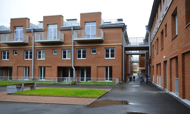 Жилой комплекс «Амазонка». Внутренний двор. Слева лоджии и палисадники больших квартир 1 этажа, справа навесные мостики к «дому-стене»