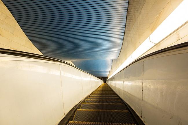 Реечная потолочная система нестандартной формы в цветовом исполнении над эскалаторами. Фотография предоставлена компанией «АСП-Технолоджи»