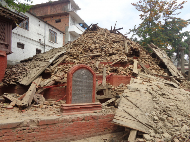Collapsed Chasin Dega at Hanuman Dhoka behind a stone plaque indicating World Heritage status © Kai Weise