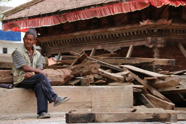 Местный житель рядом со спасенными деревянными фрагментами зданий на площади Дурбар (г. Катманду) © Kai Weise