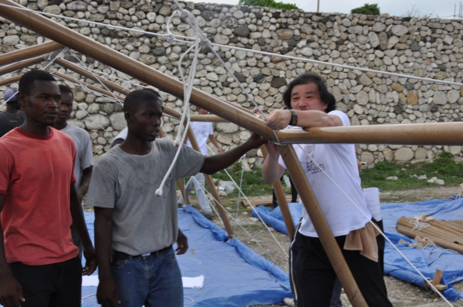 Shigeru Ban with volunteers constructing Paper Emergency Shelter in Haiti. Photo by Alex Martinez