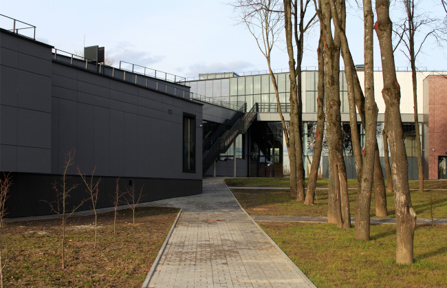 Yard with a lime tree avenue turned towards the Oka. On the left: educational work shops. On the right: the foyer. Innovation and Culture Center in Kaluga.  Photograph © Julia Tarabarina, Archi.ru
