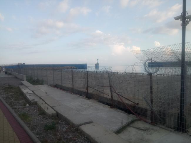 Деятельность портов регламентируется целым рядом документов. Прибрежная часть порта – охранная зона, и она огорожена забором. Фотография: Мария Трошина
