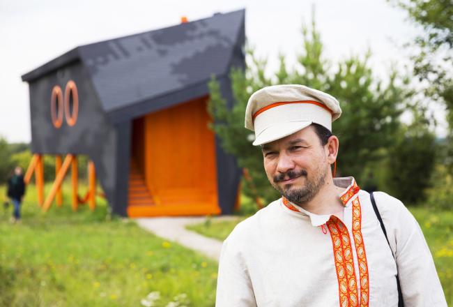 Владимир Кузьмин в образе пастуха и дом-Корова. Архи-дни в Ясно Поле. Фотография © Евгения Яровая
