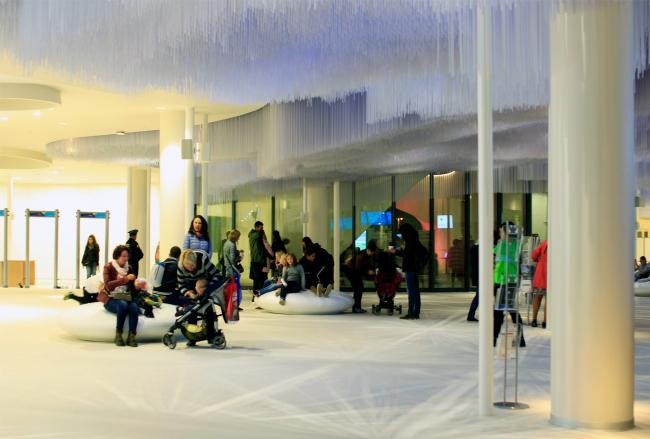 Медиа-центр, вестибюль. Очень светлый, пластиковые нити светильников занимают весь потолок; они призваны рассеивать свет: как дневной из зенитных фонарей, так и искусственный вечером. Потолок напоминает северное сияние. Парк Зарядье. Фотография © Юлия Тарабарина, Архи.ру, 09.2017