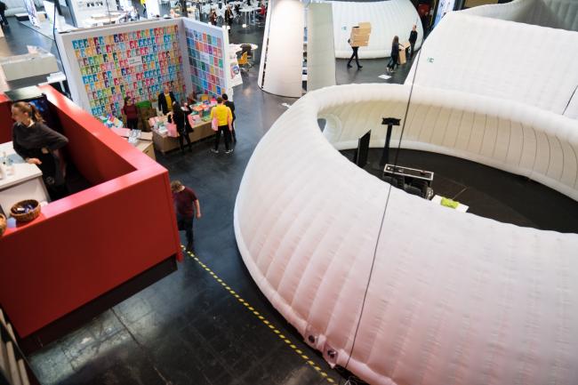 Пространство Berlin Arena было полностью занято различными стендами партнеров фестиваля и надувными павильонами для презентаций конкурсных проектов. Изображение предоставлено WAF