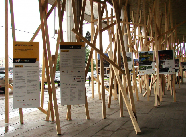 В этом году организаторы не стали экспериментировать с выставками под колоннадой – и правильно, Москва не Венеция; погода с избытком подтвердила правильность такого решения. Единственной выставкой на холоде, но среди колонн стал АРХИWOOD куратора Николая Малинина: прямо перед входом дизайнеры Савинкин и Кузьмин соорудили лес из деревянных белок, пристроив между ними планшеты номинантов на первую российскую премию деревянной архитектуры. Работы достойны, картинки красивы, приклеенные к планшетам разноцветные кружочки не случайны: это попытка интерактивного голосования среди посетителей выставки. Одновременно в интернете тоже идет голосование; все результаты будут объединены и объявлены в пятницу (то есть сегодня) вечером, в 19:00.