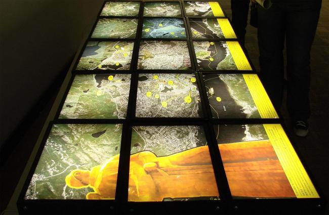Проект Мурманск CMYK демонстрируется в темноте светящимися слайдами (на этой выставке наши преимущественно светятся, а иностранцы серьезно висят себе по стенам в виде планшетов). Идеи похожи на Пермь: уменьшение города, но дополнены забавынми мелочами: светящимися ставнями для пятиэтажек, например. Рядом, такими же слайдами, демонстрируется проект «Изумрудное кольцо планеты», посвященный модернизации городов за полярным кругом. С Мурманском их объединяет оптимистическая песня мультяшного трубадура про «солнце взойдет»; для полярного круга солнце актуально.